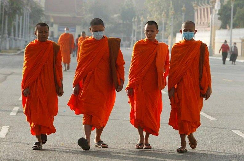 پیاده روی چندین راهب بودایی با ماسک محافظتی در نزدیکی کاخ رویال در پنوم پن، کامبوج، در روز سه شنبه ۲۸ ژانویه سال ۲۰۲۰ . کشورها برای جلوگیری از شیوع ویروس کرونا پیشگیری های لازم را انجام می دهند.