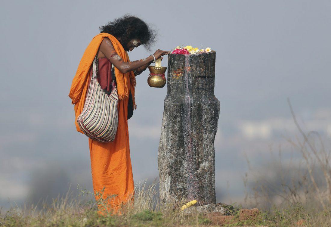 راز ونیاز مرد مقدس هندو در کنار یک لینگام، نماد شیوا، خدای آیین هندو، در جشنواره شیواراتری در حومه حیدرآباد. شیواراتری یا شب شیوا به پرستش شیوا خدای مرگ و ویرانی در آیین هندو اختصاص دارد.